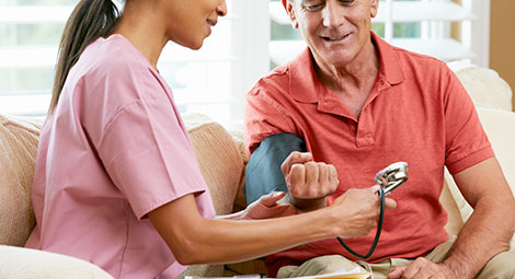 Doctor visiting patient at home. The doctor is taking the blood pressure of the patient